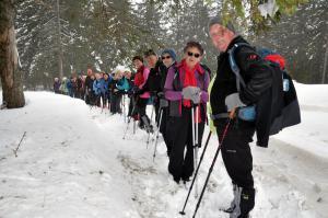 Kolona planincev med snežnimi zameti v smeri Rogle